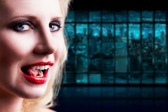 Attractive vampire licking her teeth. In front of a night scene Royalty Free Stock Images