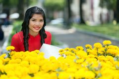 Attractive Vietnamese woman with yellow flowers Stock Image