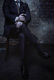 Attractive villain sitting with his legs crossed Royalty Free Stock Photography