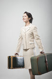 Attractive vintage woman with suitcases. Smiling vintage woman holding suitcases ready to leave for vacations Stock Photo