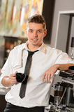 Attractive waiter leaning on espresso machine Stock Photos