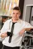 Attractive waiter leaning on espresso machine Stock Photos