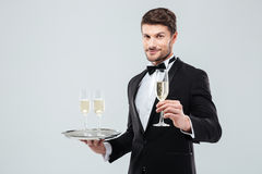 Attractive waiter in tuxedo holding tray and glass of champagne Stock Photos