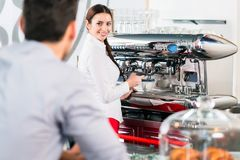 Attractive waitress smiling to male customer while preparing esp Royalty Free Stock Image