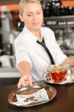 Attractive waitress taking tip in bar CZK. Attractive waitress taking tip in bar from tray czech crowns Royalty Free Stock Image