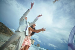 Attractive wedding couple letting go white doves at beautiful ce. Remony. Dream wedding in tropical country, caribbean or Hawaii Stock Photography