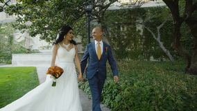 Attractive wedding pair of young people walking under big green tree stock video footage
