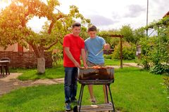 Attractive white father and son are smiling and grilling Stock Photos