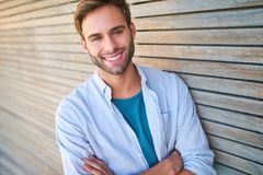 Attractive white guy smiling at camera leaning against wooden cladding. Tightly cropped image of handsome young male in his mid 20s smiling at camera with his Stock Images