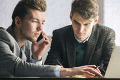 Attractive white males at workplace. Portrait of two attractive white males at workplace using laptop, talking on the phone and discussing. Teamwork concept Stock Images