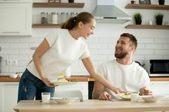 Attractive wife serving food cooked for husband in the kitchen