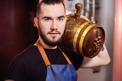 Attractive winemaker holds a wooden barrel of wine. A young attractive winemaker holds a wooden barrel of wine royalty free stock image