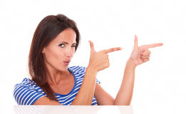Attractive winking woman pointing to her left. In white background - copyspace Royalty Free Stock Photography
