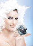 Attractive winter girl with present box. Attractive winter girl holding small present box, wearing professional makeup with strasses and white feather hat Stock Image