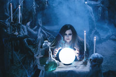 Attractive witch doing magic in the magic lair. On the eve of Halloween witch casts a spell, uttering terrible incantations on a glowing, crystal ball. Fabulous Royalty Free Stock Images