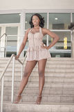 Attractive woman. Beautiful African American woman in a modern dress showing off her long legs Royalty Free Stock Image