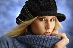 Attractive woman. Portrait of young beautiful woman in blue sweather and with black cap Stock Photography