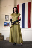 Attractive woman in 1940s clothing posing in front of flag Royalty Free Stock Images