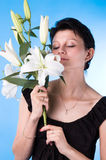 The attractive woman. With a bouquet of lilies isolated on a dark blue background Stock Photography