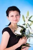 The attractive woman. With a bouquet of lilies isolated on a dark blue background Stock Photos