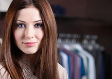 Attractive woman against the background of clothes Stock Images