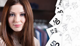 Attractive woman against the background of clothes and sale tags. Attractive woman against the background of set of hanger clothes. Sale time Stock Photography