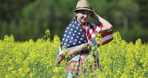 An attractive woman with an American flag with pole. Stars and stripe on her back is standing in a rapeseed field and smiling. USA flag fluttering in the wind stock footage