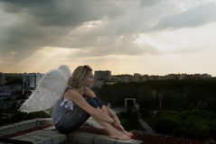 Attractive woman with angel wings on roof Royalty Free Stock Photo