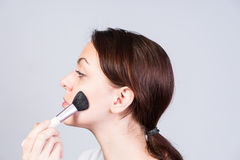 Attractive woman applying blusher to her cheek Royalty Free Stock Image