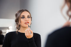 Attractive woman applying lipstick on her lips Stock Photography