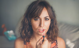 Attractive woman applying lipstick or lip gloss. Attractive woman with long brown hair applying lipstick or lip gloss to her lips with a brush to enhance and Royalty Free Stock Photos