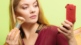 Attractive woman applying make up with brush. Royalty Free Stock Images