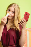 Attractive woman applying make up with brush. Young attractive woman applying make up with powder brush. Pretty gorgeous girl beautifying. Fashion and makeup Royalty Free Stock Images