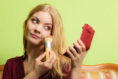 Attractive woman applying make up with brush. Stock Photo