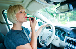 Attractive woman applying make up in her car Stock Photography
