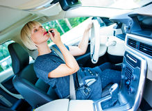Attractive woman applying make up in her car Royalty Free Stock Image