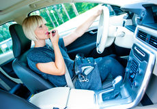 Attractive woman applying make up in her car Stock Image