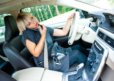 Attractive woman applying make up in her car and talking on mobi Stock Photo