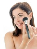 Attractive woman applying makeup to her face Royalty Free Stock Photography