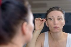 Attractive woman applying mascara to her lashes. Looking at her reflection in a bathroom mirror in a beauty and glamour concept Royalty Free Stock Photo