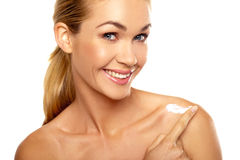 Attractive woman applying moisturiser Stock Images