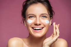 Attractive woman applying moisturizer cream on her face Royalty Free Stock Photography