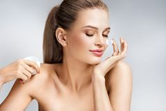 Attractive woman applying moisturizing cream on grey background. Beauty & Skin care concept Royalty Free Stock Images