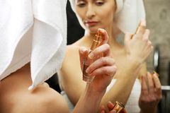 Attractive woman applying parfume. Attractive woman applying parfume in the bathroom stock photography