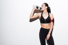 Attractive woman with armband drinking water and listening to music Royalty Free Stock Image