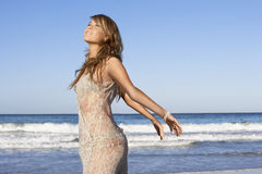 Attractive Woman With Arms Outstretched Posing By Sea Stock Image