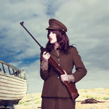 Attractive woman in army uniform carrying a rifle Stock Photos