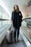 Attractive woman arriving at the airport in winter Royalty Free Stock Photo