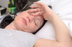 Attractive woman asleep in bed. Lying on her back with her hand to her forehead and eyes closed in a close up portrait Royalty Free Stock Images