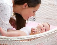 Attractive woman with baby in cot Stock Images